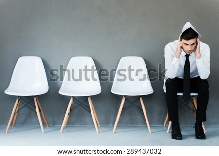 Worried about interview. Frustrated young businessman covering his head by paper while sitting on chair against grey background - stock photo