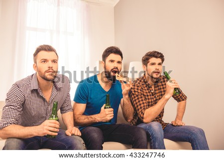 worried and concerned   men watching  tv with beer and pizza - stock photo