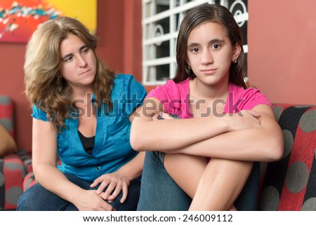 Worried and sad mother looks at her defiant teenage daughter - stock photo