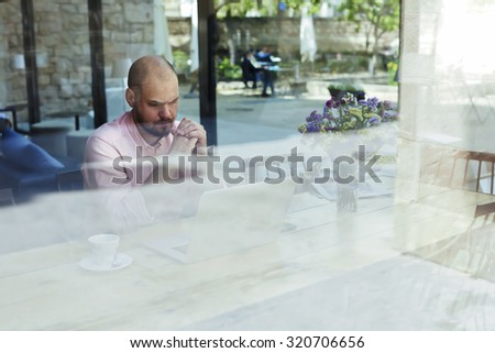 Worried and thoughtful businessman or entrepreneur sitting front open laptop computer in modern coffee shop interior in urban setting, male freelancer or student puzzled and concerned look to net-book - stock photo