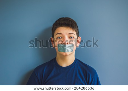 Worried boy with duct tape over his mouth - stock photo