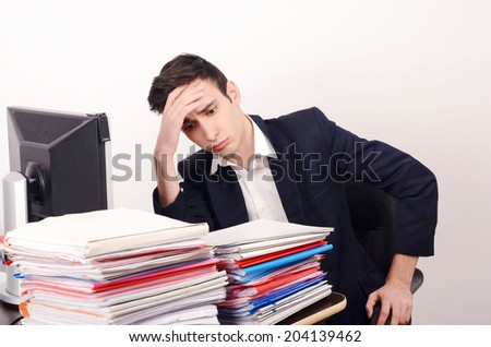 Worried business man with a lot of work. Unhappy worker with a big pile of files to work on. - stock photo