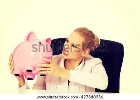 Worried business woman with a piggybank behind the desk - stock photo