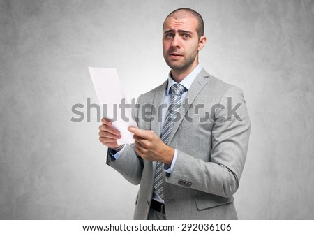 Worried businessman holding a document - stock photo
