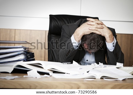 Worried businessman in dark suit sitting at office desk full with books and papers being overloaded with work. - stock photo