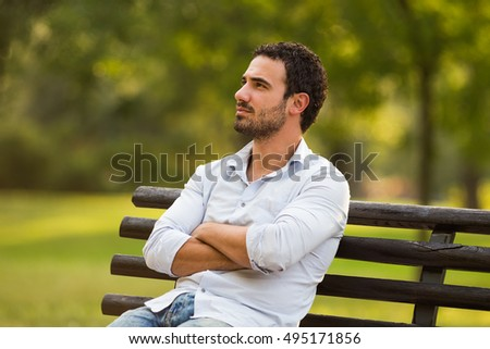 Worried businessman is sitting at the park and thinking about something.Worried businessman thinking