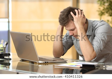 Worried businessman lamenting in front of a computer after a big mistake at office - stock photo