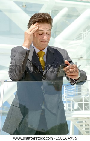 Worried businessman looking at his cellphone