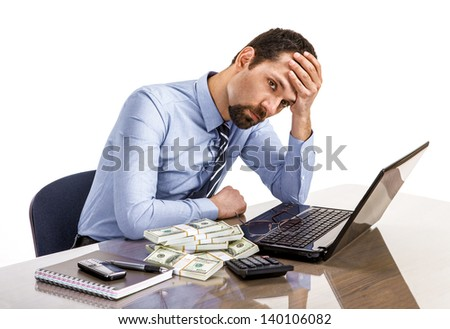 Worried businessman sitting at office desk being overloaded with work  - stock photo