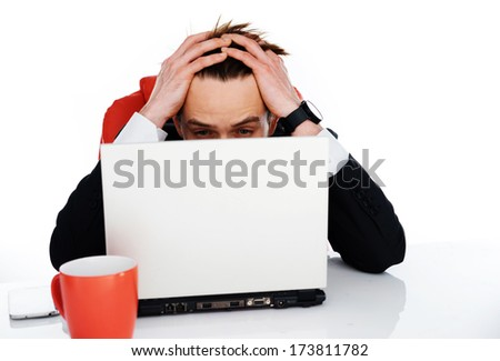 Worried businessman sitting behind his laptop computer holding his head in his hands as he stresses over a problem at work - stock photo