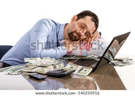 Worried businessman sleeping at office desk being overloaded with work and accounting money  - stock photo
