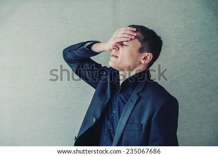 Worried businessman with hand on the head - stock photo