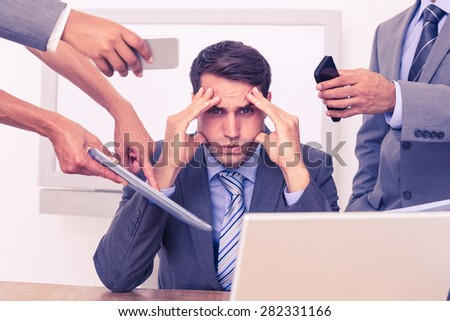 Worried businessman with head in hands sitting at the office - stock photo
