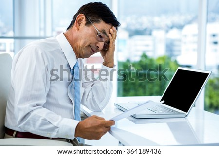 Worried businessman working at his desk in his office