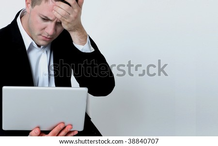 Worried businessman working on laptop