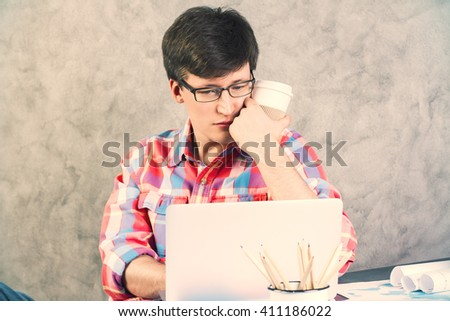 Worried caucasian man with coffee in hand next to face looking at notebook screen placed on desktop with office tools. Concrete background - stock photo