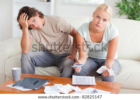 Worried couple calculating expenses in the living room - stock photo