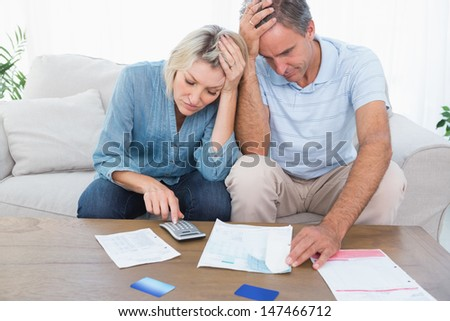 Worried couple going over finances at home in living room - stock photo