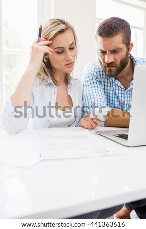 Worried couple looking at mobile phone at home - stock photo