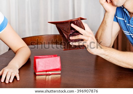 Worried couple sitting at the table with empty wallets - stock photo