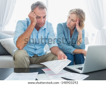 Worried couple using their laptop to pay their bills at home in the living room - stock photo