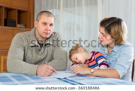 Worried couple with child sitting at the table with financial documents  - stock photo