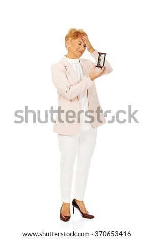 Worried elderly business woman with palm on her forehead holding hourglass - stock photo