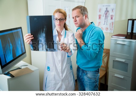 Worried female doctor with handsome male patient looking at x-ray at office. Doctor talking to her patient and showing radiograph. - stock photo
