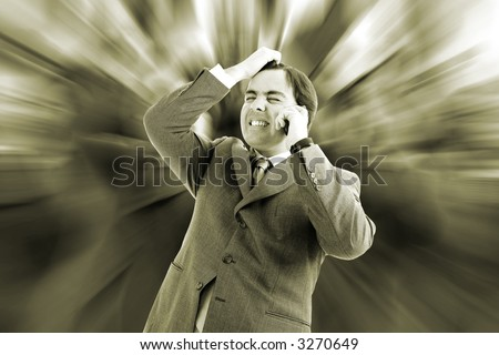 Worried, freaked-out business man pulling his hair while yelling at a cell phone. - stock photo