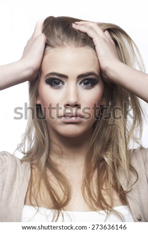 Worried girl, hands in messed up hair - stock photo