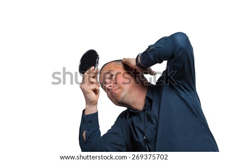 Worried guy having a closer look at his balding head - stock photo