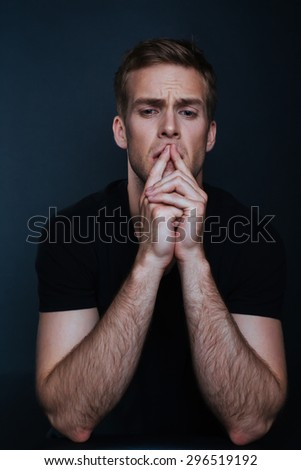 Worried handsome man in a black shirt is trying to figure out how to solve the problem on a dark background