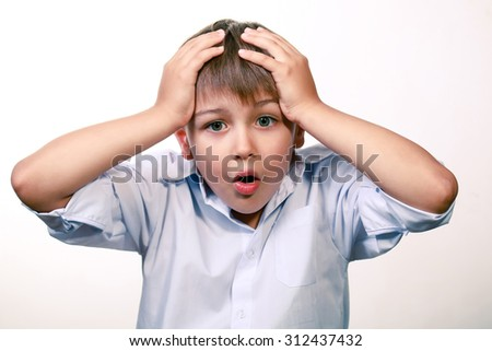 Worried kid grabbed his head with his hands - stock photo