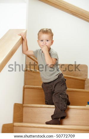 Worried little boy standing on stairs, leaning on hand rail.