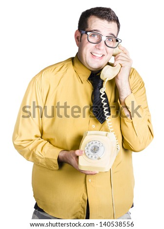 worried looking man on an old fashioned corded phone, taking important call - stock photo