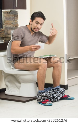 worried man sitting on the toilet with last sheet of toilet paper - stock photo