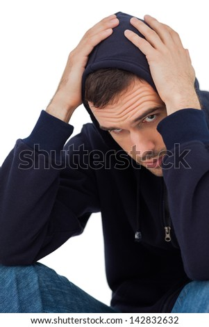 Worried man with head in hands on white background - stock photo