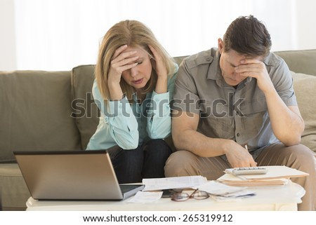 Worried mature couple with hand on head calculating home finances on sofa at home