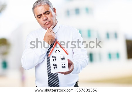 worried mature man holding a house - stock photo