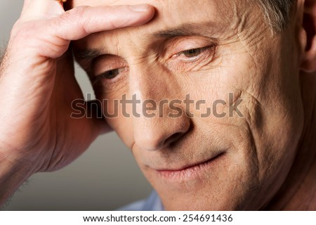 Worried mature man touching his head. - stock photo