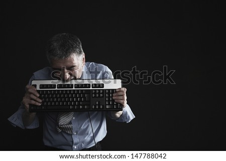 Worried middle aged businessman biting computer keyboard against black background - stock photo