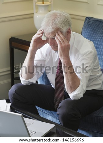 Worried middle aged businessman with laptop sitting on sofa - stock photo