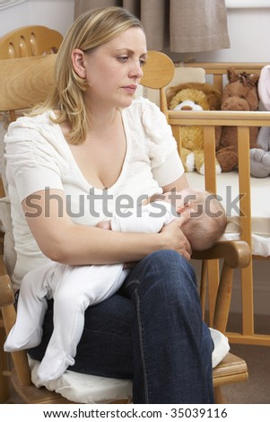 Worried Mother Breastfeeding Baby In Nursery - stock photo
