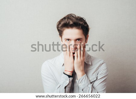 Worried or ashamed man covering his face with hand - stock photo