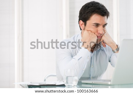 Worried pensive business man watching at his laptop at office - stock photo