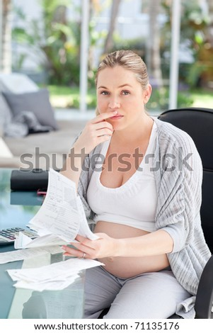 Worried pregnant woman calculating her domestic bills at home - stock photo