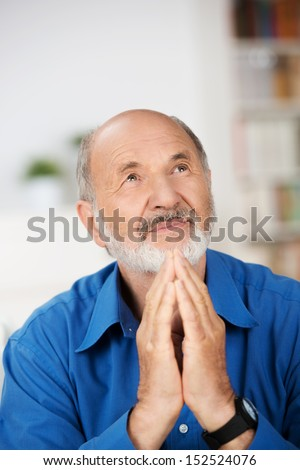 Worried religious senior man praying to god with his hands raised and touching as he looks beseechingly towards heaven for help and inspiration - stock photo