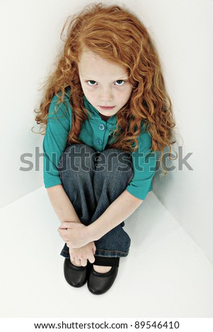 Worried sad young girl child sitting alone in corner. - stock photo