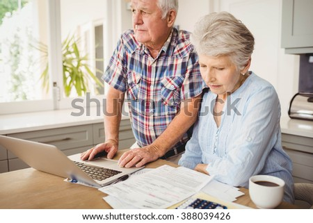 Worried senior couple checking their bills at home - stock photo