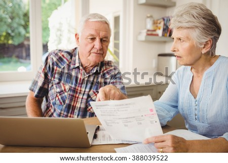 Worried senior couple discussing their bills at home - stock photo